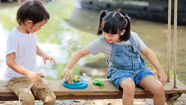 Niños jugando en un columpio con juguetes de Plantoys, en CuCuToys