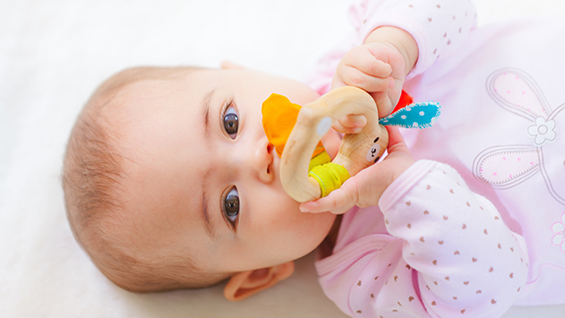 Bebé con sonajero mordedor de madera ecológica de Plantoys, en CuCuToys